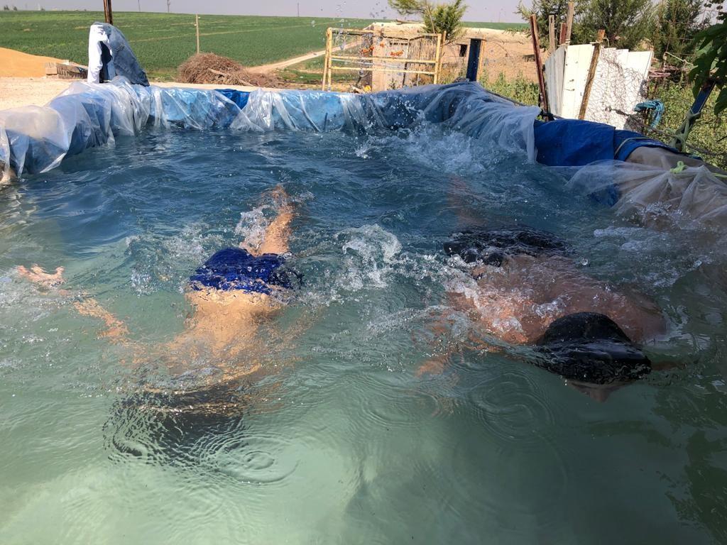 Kızıltepe'de sıcaktan bunulan çocuklar çareyi brandadan yapılan havuzda arıyor